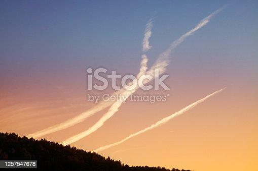 Plane vapour trails, mountainous landscape, sunset background. Ourense province, Galicia, Spain.