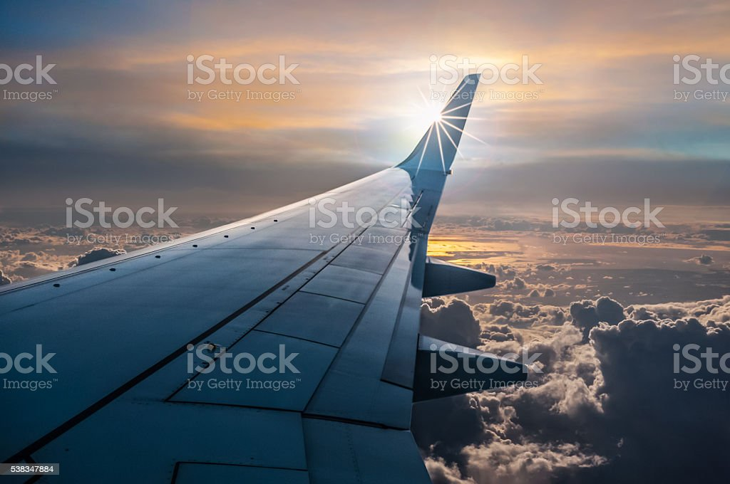 Plane View A view out of the window of an Airplane. The sun is just behind the wing and flying above the clouds. Activity Stock Photo
