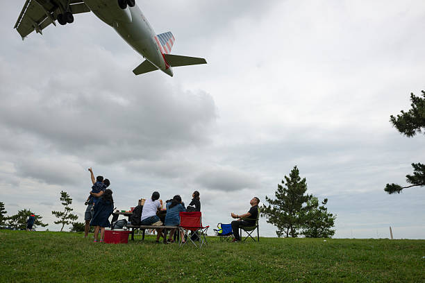 Plane watching at Gravelly Point in Arlington, Virginia Arlington, Virginia, USA - July 3, 2016: At Gravelly Point in Arlington, Virginia, a family looks up as an American Airlines jet, an Airbus A319, passes overhead moments before touching down at Ronald Reagan Washington National Airport. ronald reagan washington national airport stock pictures, royalty-free photos & images