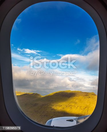 Plane window view of landing at Vagar airport on Faroe Islands with aircraft engine in the foreground and blue sky with clouds in the background.