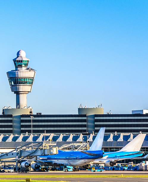 planes waiting at a terminal in an airport - schiphol stockfoto's en -beelden
