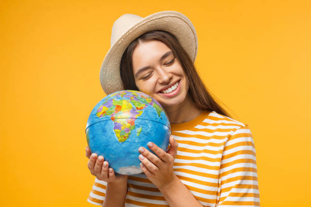 planet care, save the earth concept. cheerful young woman hugging globe, isolated on yellow background - earth day stock pictures, royalty-free photos & images