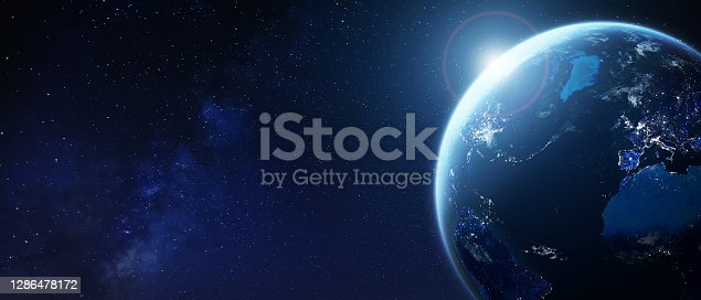 Planet Earth from space with city lights in Europe and North America. World with sun and star background. Banner for global business, international finance, fintech technology, elements from NASA