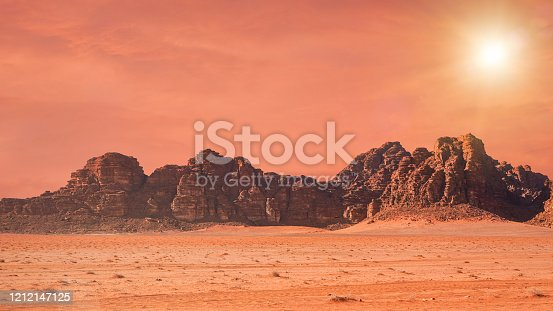 Planet Mars like landscape - Photo of Wadi Rum desert in Jordan with red colour filter and added sun, this location was used as set for many science fiction movies.