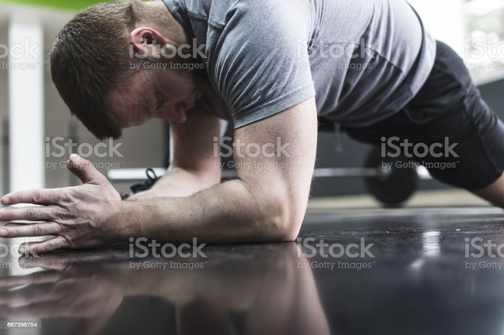 Plank it! Confident muscled young man wearing sport wear and doing plank position stock photo
