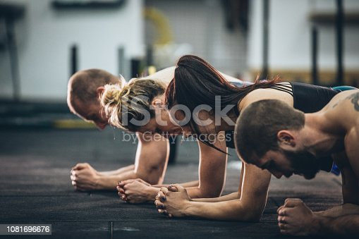 Four people doing plank exercise at the gym