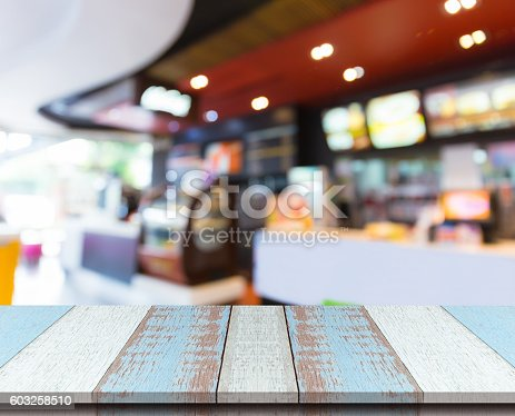 istock Plank wood table top with blurred bakery coffee shop background. 603258510