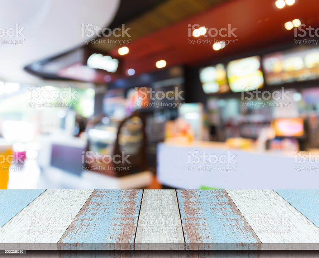 Plank wood table top with blurred bakery coffee shop background. stock photo