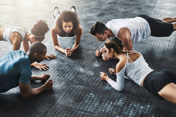 Planking - so simple, so effective Shot of a group of young people doing planks together during their workout in a gym exercise class stock pictures, royalty-free photos & images
