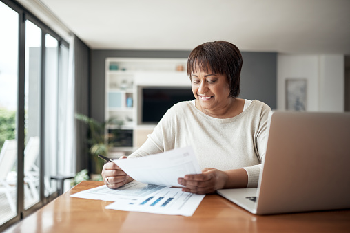 Cropped shot of a happy senior woman sitting alone in her living room and going through paperwork