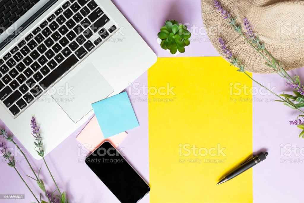 Planning a vacation. Laptop, notebook and flowers. view from above. Working space. Purple background and lavender flowers. Workplace of a woman. stock photo
