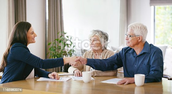 Shot of a senior couple meeting with a consultant to discuss paperwork at home