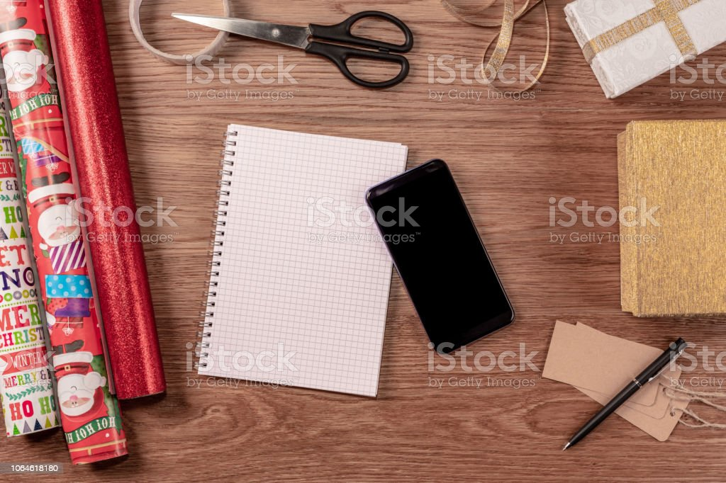 Planning for Christmas with a notepad and smartphone stock photo