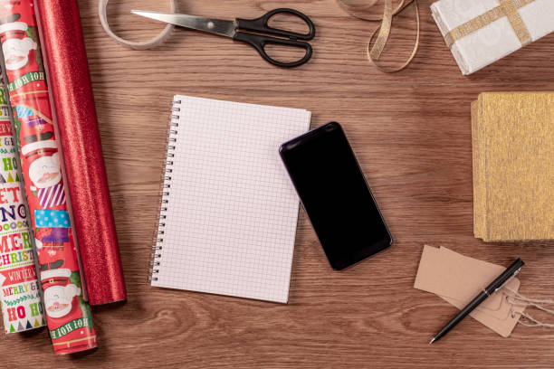 planning for christmas with a notepad and smartphone - christmas stock photos and pictures