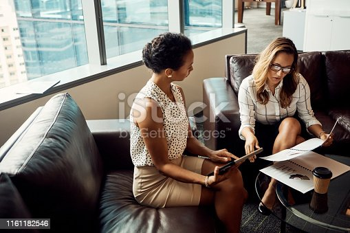 High angle shot of two young businesswomen using a digital tablet while going over some paperwork in their office