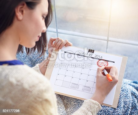 Shot of a young woman circling the first of January on a calendar