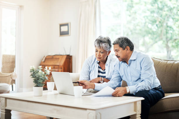 Planning our retirement together Shot of a senior couple using a laptop together at home plan document stock pictures, royalty-free photos & images