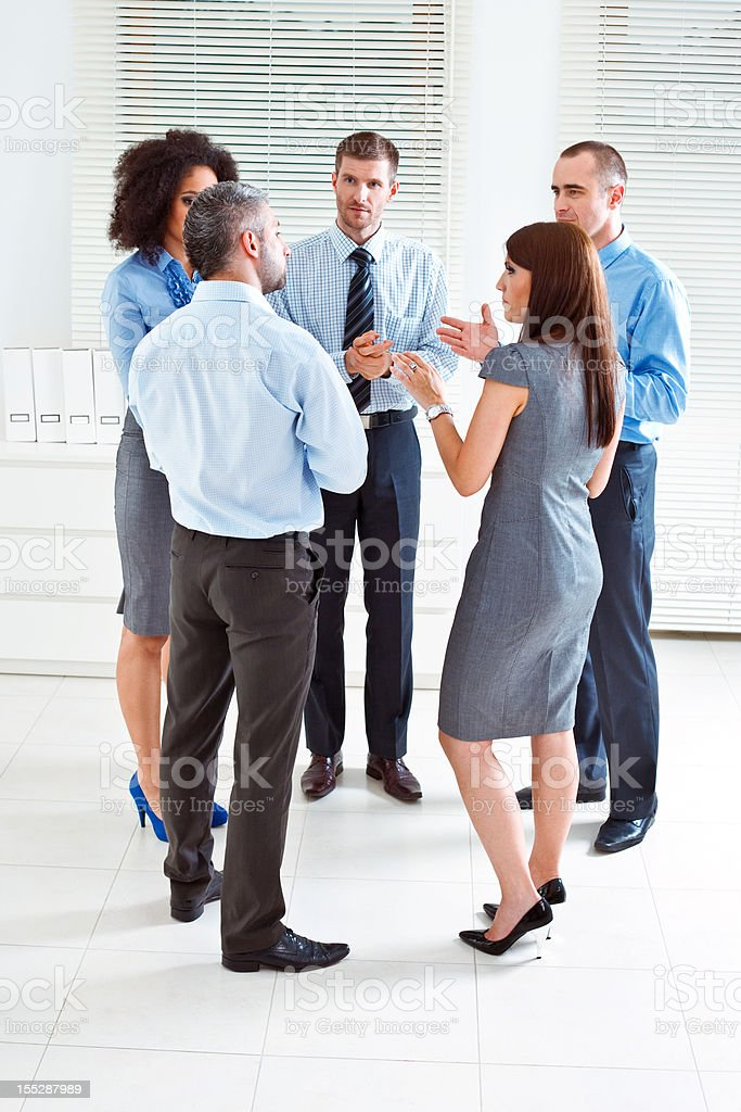 Planning Five serious business people standing in an office and having conversation. 25-29 Years Stock Photo