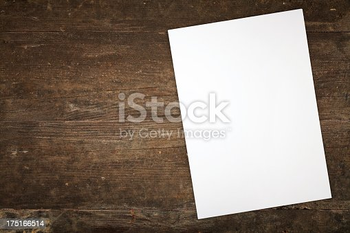 Directly above view of a table with blank papers on it.The table is made of dark wood.The table seems old. The paper is very white.The image has a horizontal layout.The table is dirty.The image is a close-up because the paper is not complete.