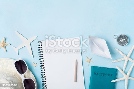 istock Planning summer holidays and trip vintage background. Travelers notebook with tourism accessories on blue desk top view. 936373320