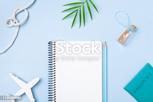 936373320 istock photo Planning summer holidays, tourism and vacation background. Travelers notebook with accessories on blue pastel table top view. Flat lay. 1150482880