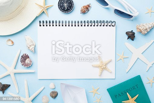 936373320 istock photo Planning summer holidays, tourism and vacation background. Travelers notebook with accessories on blue desk top view. 941391580