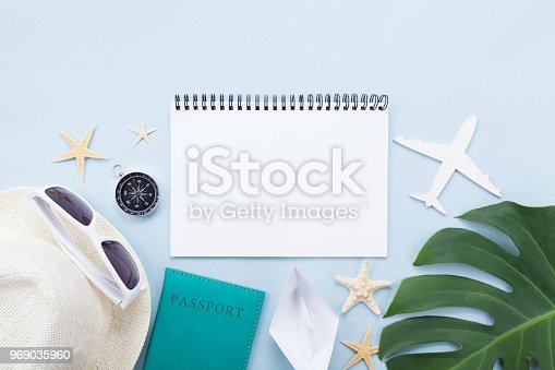 936373320 istock photo Planning summer holidays, tourism and vacation background. Travelers notebook with accessories on blue pastel table top view. 969035960