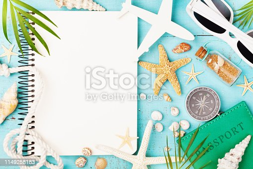 936373320 istock photo Planning summer holidays, trip, travel and vacation background. Open notebook with accessories on blue table top view. 1149258183