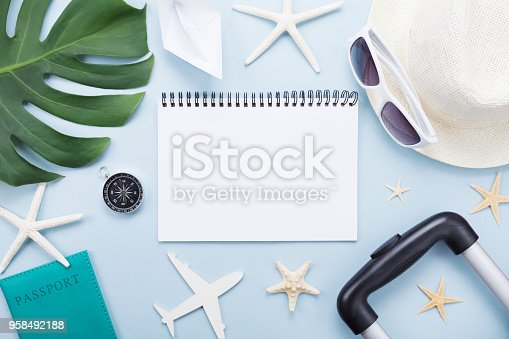 936373320 istock photo Planning summer holidays, vacations and trip. Travelers notebook with tourism accessories on blue table top view. 958492188