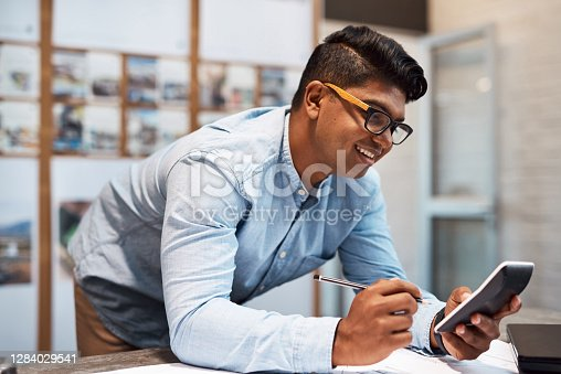 Shot of a young architect using a calculator while drawing up a building plan