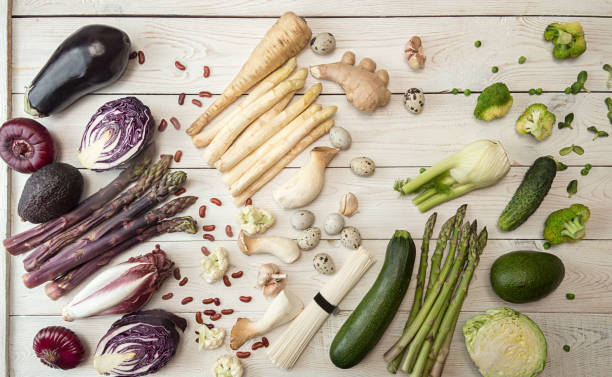 Plant based modern flat lay big set collection rows of white red purple green vegetables on white background. Asparagus, red cabbage, avocado, eggplants, onion stock photo