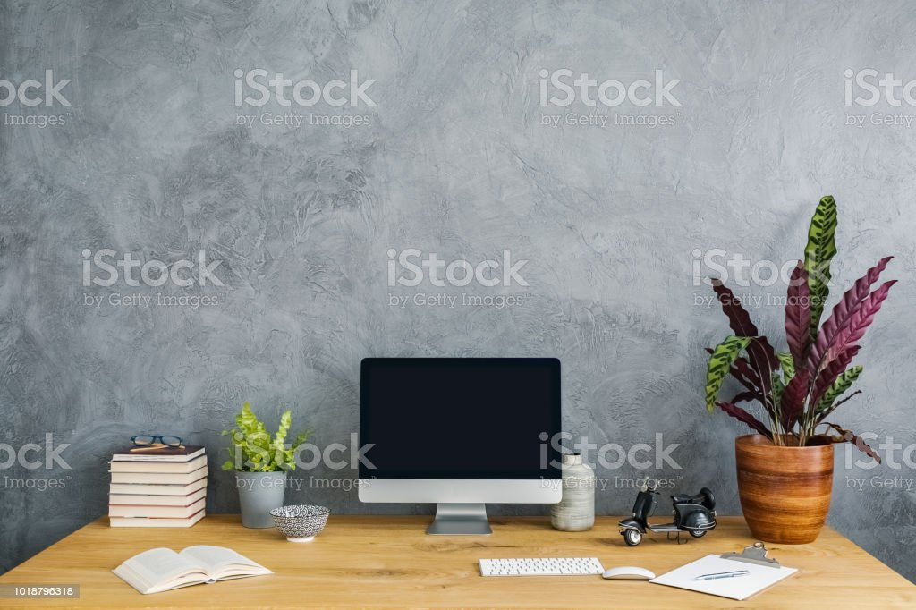 Plant, computer and books on a wooden desk set on a grey wall....