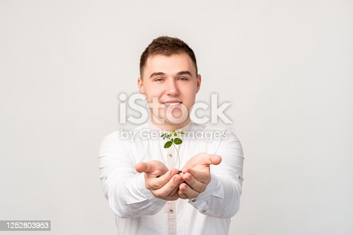 Plant in hands. Sustainable earth. Friendly man showing growing seedling isolated on blur white background.