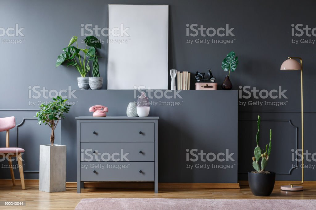 Plant next to grey cabinet with pink phone in living room interior with mockup of poster stock photo