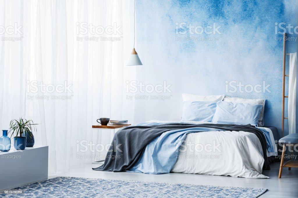 Plant on white cupboard in spacious blue bedroom interior with grey blanket on bed stock photo