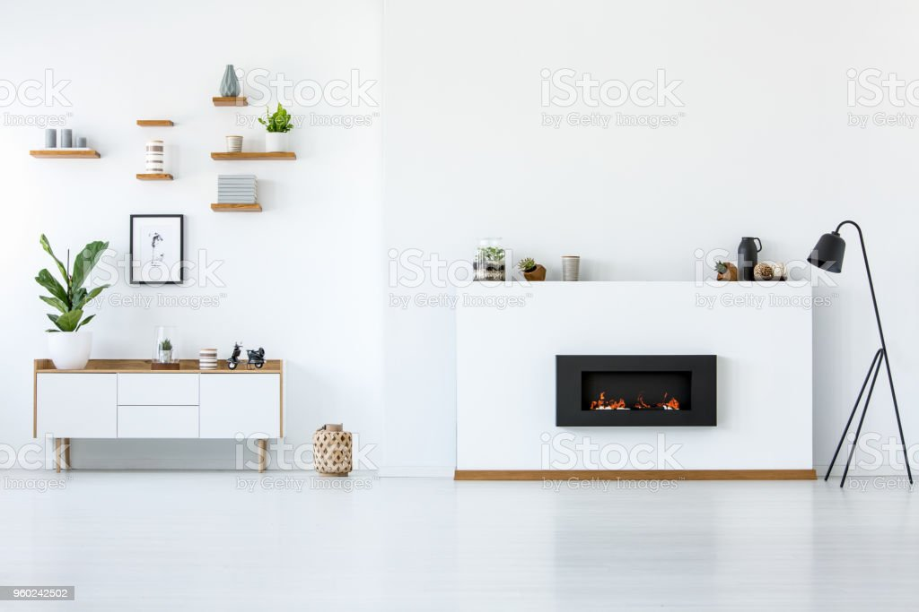 Plant on wooden cupboard in white apartment interior with copy space above fireplace. Real photo stock photo