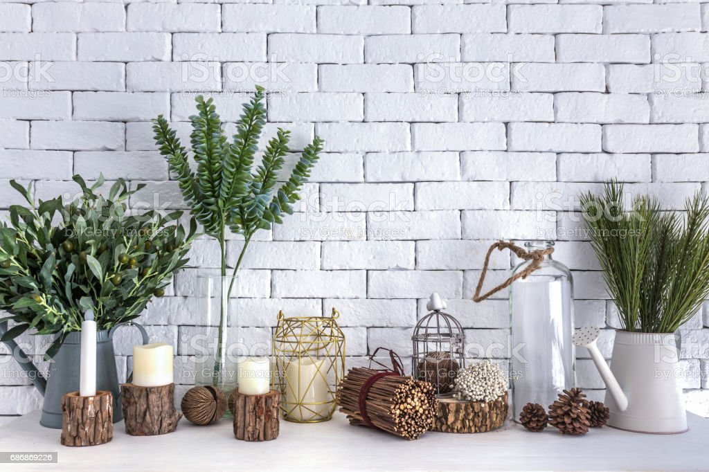 Plant pot, branch, flowers, candlelight and glass of bottle decorations on white table and brick wall background. stock photo