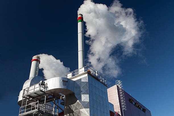 a plant pumping out smoke into the air - cogeneration plant stock photos and pictures