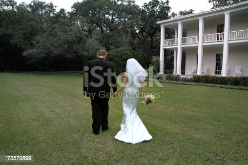 Bride and groom stroll on the grounds of a southern plantation after they say their vows at an outdoor ceremony.  Bride wearing a mermaid-style wedding dress.