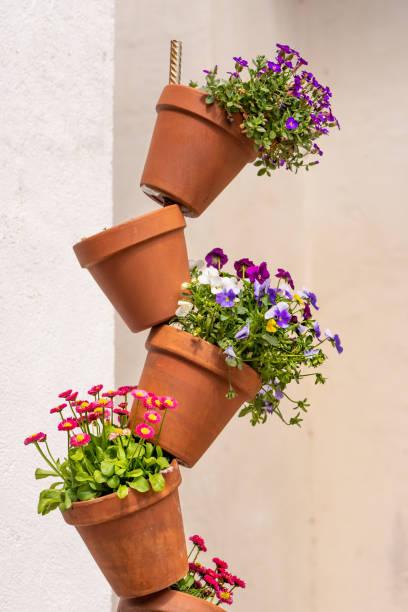Gepflanzt bunte Blumentöpfe als Dekoration vor einer weißen Wand gestapelt – Foto
