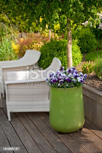 Pansies in a green planter on a deck.