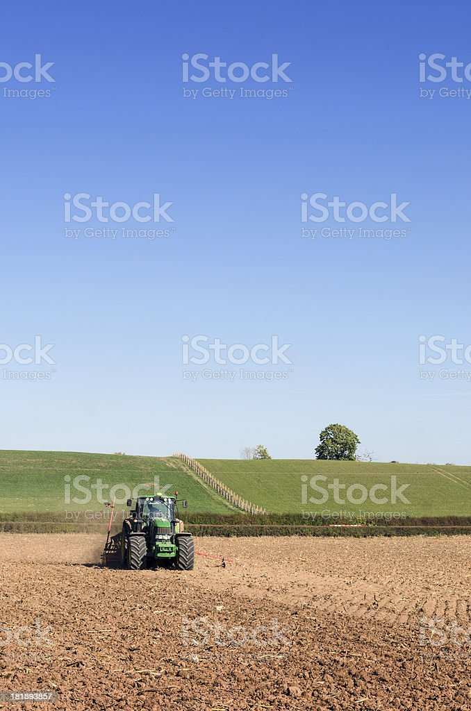 Planting crops, tractor pulling a seed drill across field stock photo