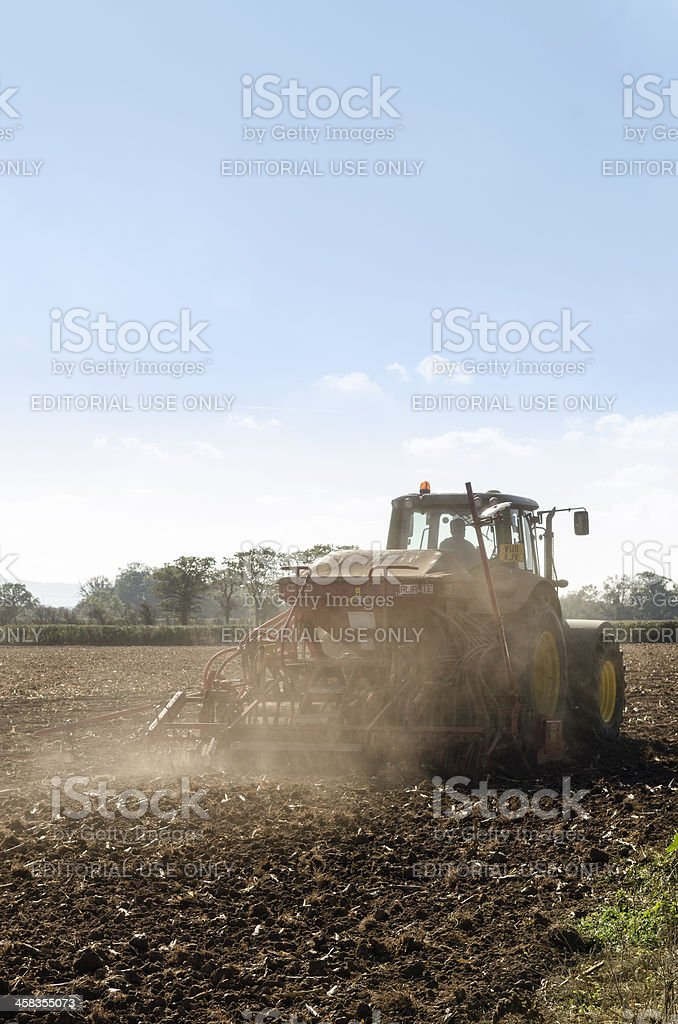 Planting crops, tractor pulling a seed drill stock photo