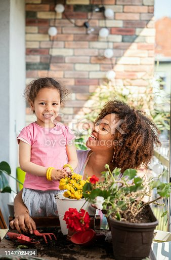 Mother and daughter planting together on balcony