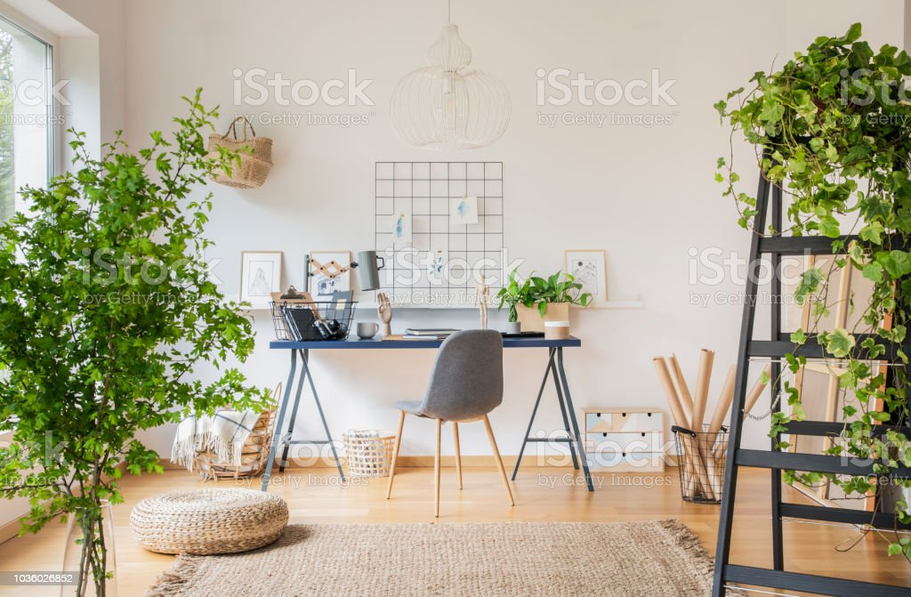 Plants In White Spacious Home Office Interior With Pouf On Carpet