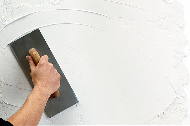 plaster application hand holding plastering tool plaster stock pictures, royalty-free photos & images