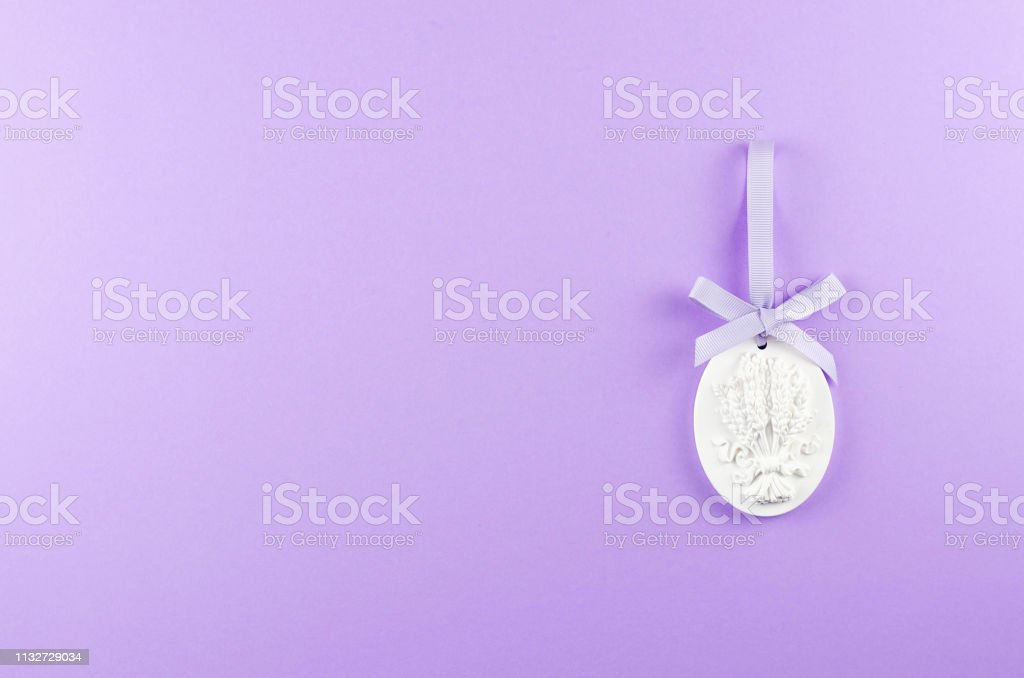 Plaster figurine with textural sprigs of lavender on a purple background. - Стоковые фото 2010 роялти-фри