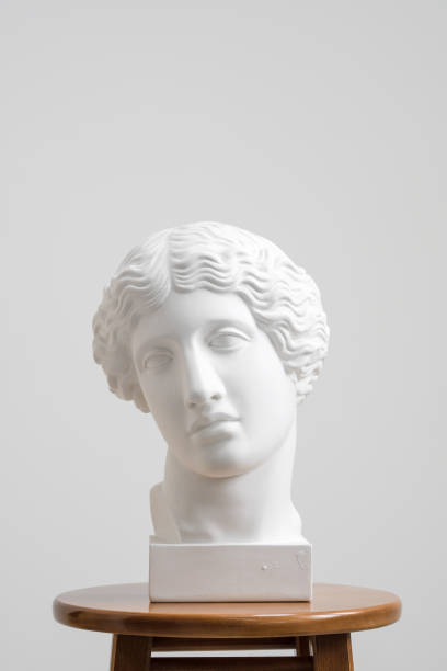 plaster head, antique sculpture for learning to draw. standing on a stool on a white background. - statua foto e immagini stock