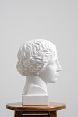 Plaster head, antique sculpture for learning to draw. Standing on a stool on a white background.