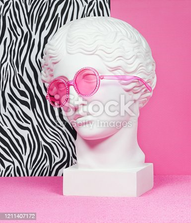 Plaster head model (mass produced replica of Head of an Amazon) wearing pink eyeglasses